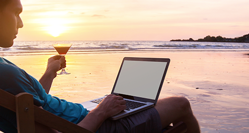 businessman working on beach with drink using cloud technology solutions